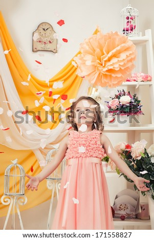 Fashionable little girl throwing petals in studio