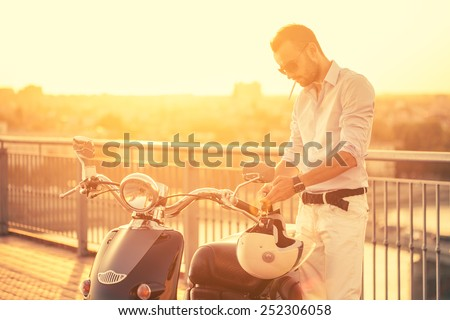 Fashionable macho man parking his classic motorbike to have a cigar during sunset.  - stock photo