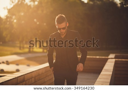 Fashionable man dressed in a black suit and sunglasses. a successful entrepreneur - stock photo