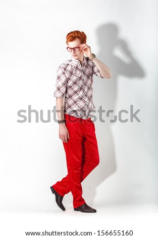 Fashionable man in red trousers posing looking back - stock photo