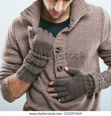 Fashionable man in winter knitted clothes. Studio portrait - stock photo