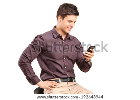 Fashionable man texting by a cell phone isolated on white background