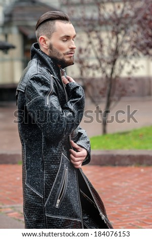 Fashionable man with beard in leather coat standing in the street. Posing for street fashion photographer in the nude. Perfect body model in leather pants leather jacket