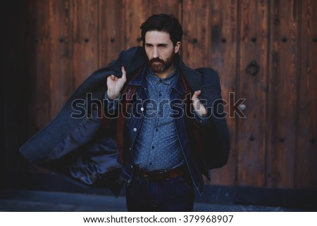 Fashionable mature male with beard holding coat on his shoulders while posing outdoors in autumn season, trendy adult hipster man dressed in modern clothes standing outside near brown wooden wall