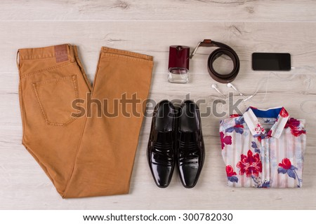 Fashionable men's set of clothes and accessories on a wooden background. - stock photo