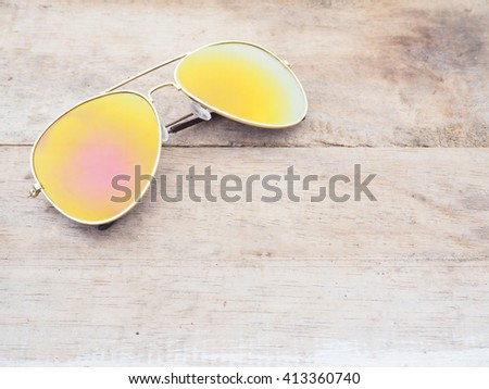 Fashionable mirror sunglasses on wooden background - stock photo