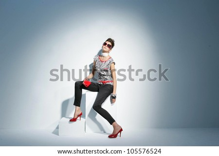 fashionable model in sunglasses on the wooden cube. - stock photo