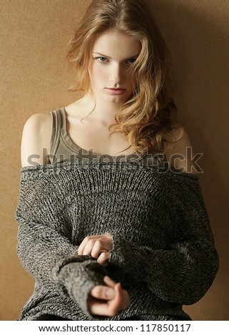 fashionable model with curly hair over the wooden background. daylight. studio shot