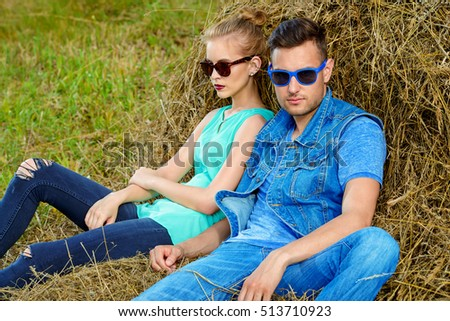 Fashionable models wearing jeans clothes posing in haystack. Denim style.