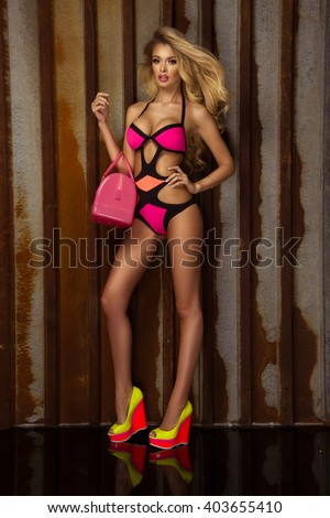 Fashionable photo of attractive young blonde beauty posing in pink swimwear, looking at camera. - stock photo