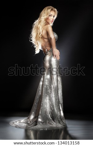 Fashionable photo of beautiful elegant young woman wearing a silver sequined evening dress with her hands on her hips. Healthy long blonde hair. - stock photo