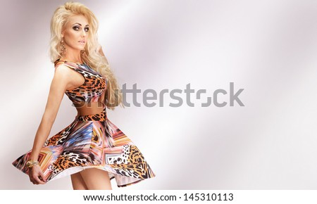 Fashionable photo of beautiful sensual blonde woman dancing, wearing dress, looking at camera.