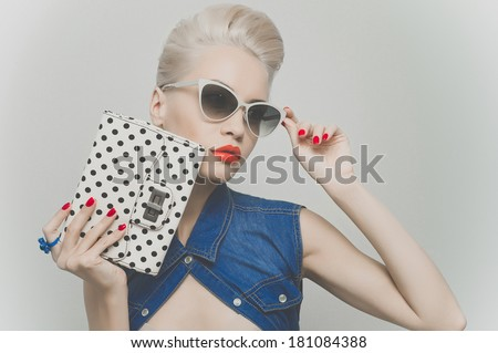 Fashionable photo of young stylish blonde in denim vest - stock photo