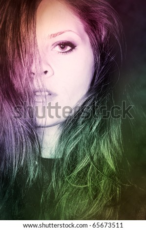 Fashionable portrait of a young woman with artistic lighting in rainbow colors.