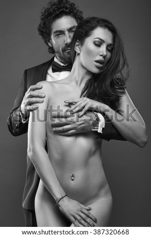 Fashionable portrait of elegant sexy couple in studio. Brutal man in suit hugging a naked woman from behind on dark background. Grayscale - stock photo