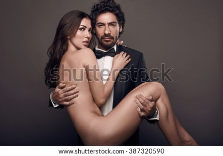Fashionable portrait of elegant sexy couple in studio. Naked beautiful woman at the hands of a brutal man in suit on dark background - stock photo