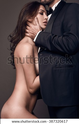 Fashionable portrait of elegant sexy couple in studio. Naked beautiful woman hugging a brutal man in suit on dark background