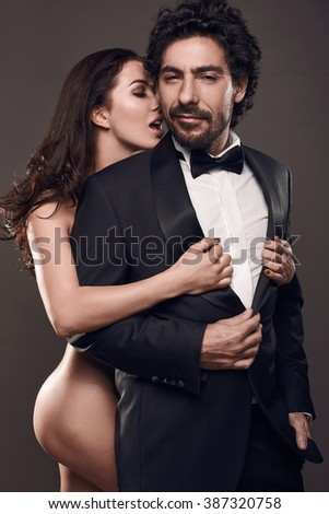 Fashionable portrait of elegant sexy couple in studio. Naked beautiful woman touching a brutal man in suit on dark background - stock photo
