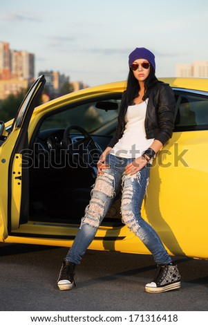 Fashionable punk woman standing at the car - stock photo