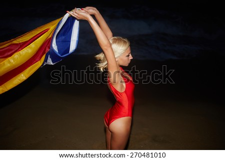 Fashionable sexy woman with arms up posing on the ocean beach at night holding Catalonia flag, blond caucasian girl with beautiful figure feeling so free enjoying nature at sea coastline - stock photo