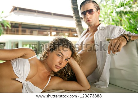 Fashionable sexy young couple lounging on an outdoors tropical bed in an exotic hotel spa garden, relaxing together. - stock photo