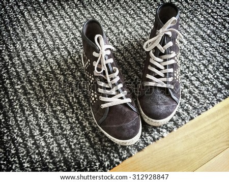 Fashionable shoes with metal rivets on gray striped carpet.