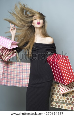 Fashionable shopping girl with streamed hair in the breeze in black dress holding colorful packages and box, vertical picture