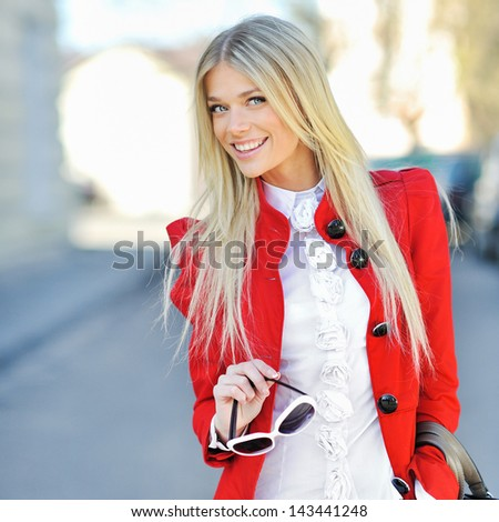 Fashionable smiling young girl in red dress with handbag outdoor - stock photo