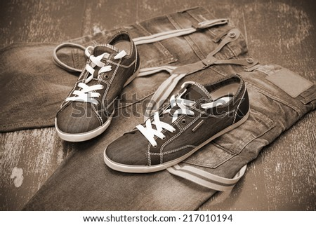 fashionable sneakers and jeans, photo toning in sepia - stock photo