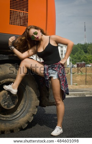 Fashionable sportive girl posing next to an excavator on a construction site