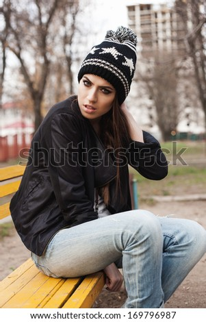 fashionable stylish girl in black beanie and leather jacket sitting on bench. Outdoors, lifestyle