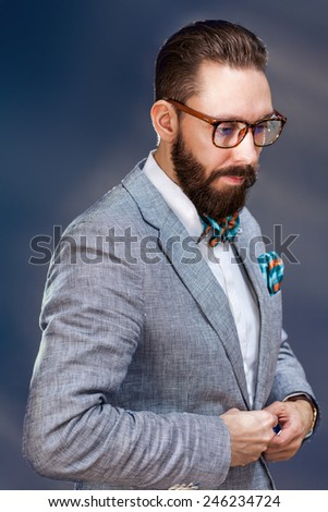 Fashionable stylish young bearded man with glasses and in a striped jacket and bow tie. - stock photo