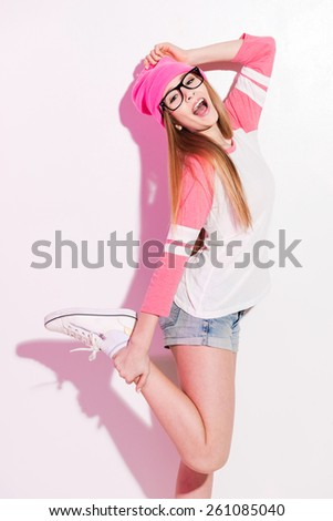 Fashionable teen. Playful young woman in pink headwear and eyewear posing against white background - stock photo