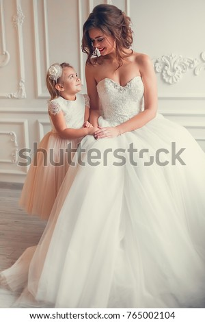 Fashionable Tender Gorgeous Portrait Of Elegant Mother Bride In Wedding  Dress With Her Cute Little Daughter