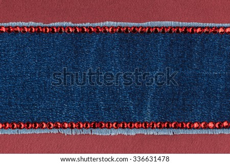 Fashionable  texture,  jeans and red  rhinestones on a red silk, with space for your text
