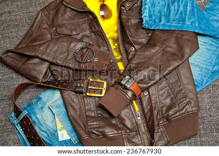 fashionable unisex outfit: leather jacket, T-shirt, jeans with a leather belt, watches, bracelets, sunglasses. Banknote 5 Euro - stock photo