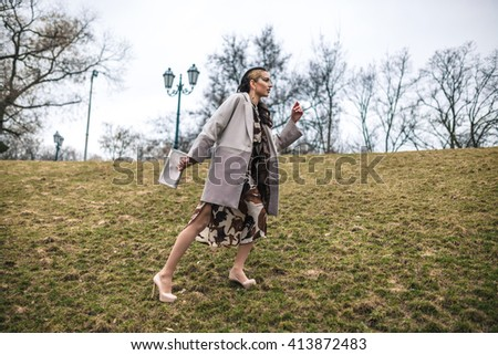 Fashionable walk. Stylish lady is walking in a park. She is wearing high hills, motley dress and white jacket.