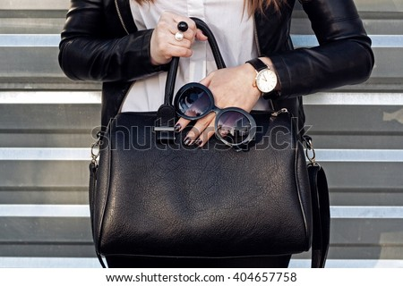 Fashionable woman hold big black handbag , accessories, sunglasses, watch. Street style city wall background