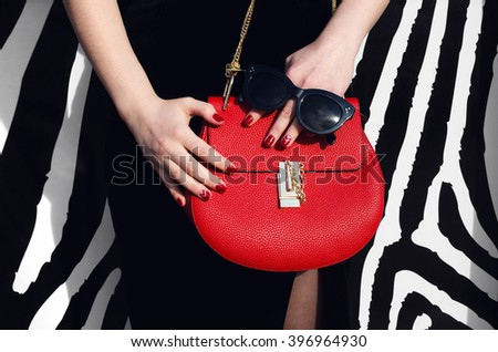 fashionable woman hold red leather handbag black sunglasses in black dress near striped wall - stock photo