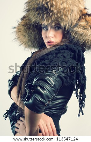Fashionable woman in a fur hat and a leather jacket. Winter style. - stock photo