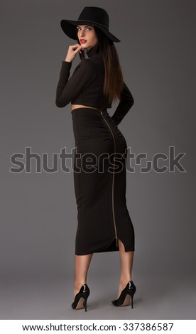 Fashionable woman in a hat, long dress, accessories, high heels, posing in studio. Fashion autumn photo