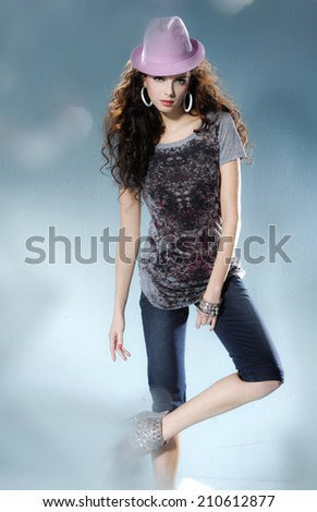 fashionable woman in a hat posing in light background