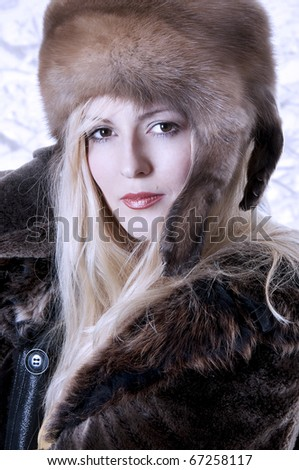 Fashionable woman in fur clothes. Portrait of seductive young blond model.