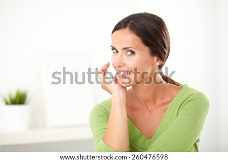 Fashionable woman in green shirt smiling and looking satisfied at indoor - copyspace - stock photo
