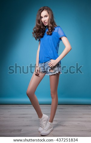 Fashionable woman in stylish clothes, studio, background blue.Young woman in stylish clothing, studio picture