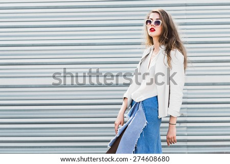 fashionable woman in sunglasses on a sunny day on the background wall - stock photo