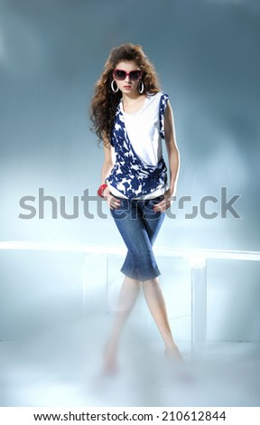 fashionable woman in sunglasses posing in light background - stock photo