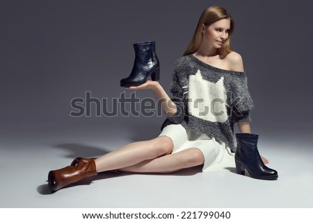 Fashionable woman in sweater, boots and autumn clothes, posing in studio holding shoes - stock photo