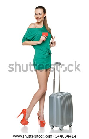 Fashionable woman in with travel bag showing blank credit card and gesturing thumb up, against white background - stock photo