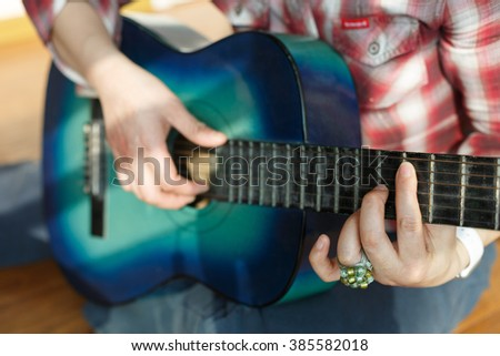 Fashionable woman is playing the guitar scene